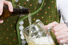 Крупный план пива баварского человека лить в стекле Стоковое Изображение RF