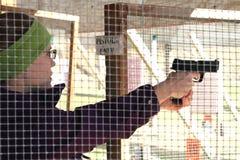 Крупный план пистолета стрельбы молодой женщины на стрельбище Стоковые Фотографии RF