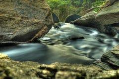Крупный план потока воды двигая через утесы Стоковые Изображения RF