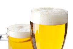 Крупный план подрезал кружки пива с пеной на белизне Стоковое фото RF