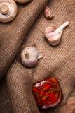 Крупный план пряного чеснока, белых ароматичных shampinions, перца красного chili в опарнике на светлой деревянной предпосылке Стоковые Фото