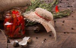 Крупный план пряных перцев chili в опарнике, раковины яичек триперсток и душистое розмариновое масло на светлой деревянной предпо Стоковое фото RF