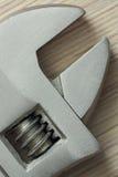 Крупный план регулируемого ключа на деревянной предпосылке Стоковая Фотография