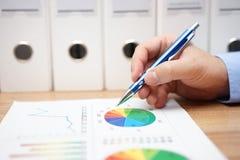 Крупный план руки бизнесмена анализируя различные финансовые диаграммы Стоковые Фото