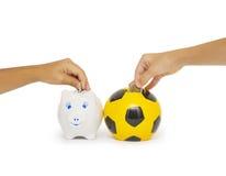 Крупный план руки женщины вводя монетку в moneybox Стоковая Фотография