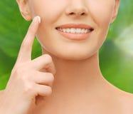Крупный план руки женщины прикладывая moisturizing сливк Стоковое Изображение RF
