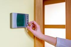 Крупный план руки женщины устанавливая комнатную температуру на режиме Стоковые Фотографии RF