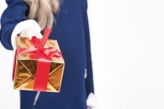 Крупный план руки маленькой белокурой девушки давая подарочную коробку рождества Стоковая Фотография