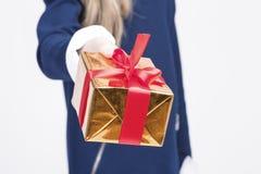 Крупный план руки маленькой белокурой девушки давая подарочную коробку рождества Стоковое Изображение RF