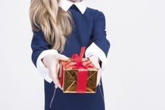 Крупный план руки маленькой белокурой девушки давая подарочную коробку рождества Стоковое Изображение