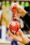 Крупный план рук держа красный шарик орнамента покрашенный стоковая фотография rf