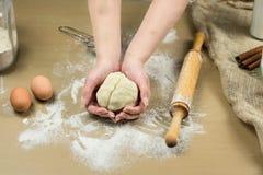 Крупный план рук женского хлебопека замешивая тесто в хлебопекарне Стоковое Фото