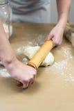 Крупный план рук женского хлебопека замешивая тесто в хлебопекарне Стоковые Изображения RF