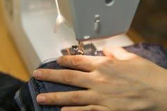 Крупный план рук женщина yong на швейной машине, шить t Стоковая Фотография