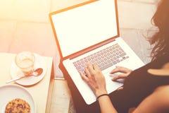 Крупный план рук женщины печатая текст на клавиатуре портативного компьютера во время перерыва на чашку кофе Стоковое фото RF