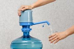 Крупный план рук лить воду в стекло от бутылки с pum стоковые фотографии rf