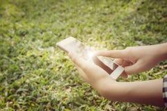 Крупный план рук молодой женщины используя smartphone Backgrou природы Стоковые Фото
