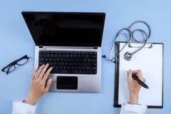 Крупный план рук доктора используя компьтер-книжку Стоковое Изображение RF