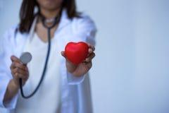 Крупный план рук доктора молодой женщины с формой сердца шарика Стоковое Фото