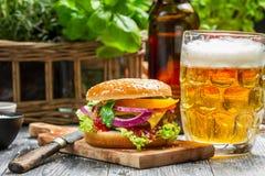 Крупный план свежего бургера и холодного пива Стоковые Фотографии RF