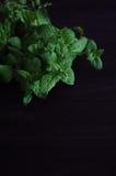 Крупный план свежей мяты снопа зеленый на деревенской доске темного коричневого цвета деревянной Стоковые Изображения