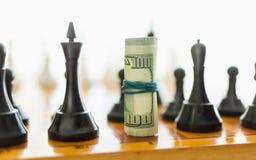Крупный план свернутых долларов на шахматной фигуре черноты места o Стоковые Изображения
