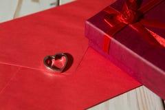 Крупный план серебряного шкентеля сердца на красных конверте и подарочной коробке Стоковые Изображения