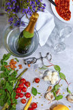 Крупный план серой таблицы с плитой, шампанским, томатами, спаржей, стеклами, штопором, фасолями на серой предпосылке Стоковые Фотографии RF