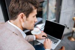 Крупный план серьезного бизнесмена используя современную компьтер-книжку в кофейне Стоковая Фотография