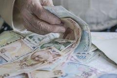 Крупный план сморщенной руки подсчитывая банкноты турецкой лиры Стоковая Фотография RF