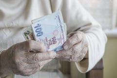 Крупный план сморщенных рук держа банкноты турецкой лиры Стоковые Изображения RF