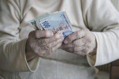 Крупный план сморщенных рук держа банкноты турецкой лиры Стоковые Изображения