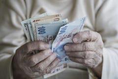 Крупный план сморщенных рук подсчитывая банкноты турецкой лиры Стоковая Фотография