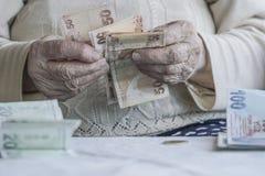 Крупный план сморщенных рук подсчитывая банкноты турецкой лиры Стоковые Изображения RF