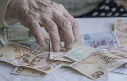 Крупный план сморщенных рук подсчитывая банкноты турецкой лиры Стоковое Изображение
