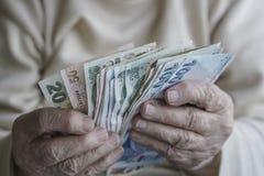 Крупный план сморщенных рук подсчитывая банкноты турецкой лиры Стоковое фото RF