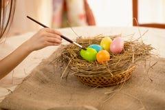 Крупный план снял девушки держа paintbrush крася пасхальные яйца Стоковая Фотография RF