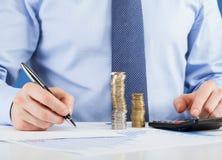 Крупный план снял рук подсчитывая монетки и делая примечания на бумаге Стоковые Изображения