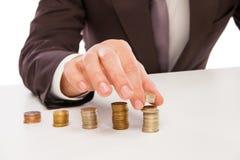Крупный план снял рук подсчитывая монетки над белизной Стоковые Изображения
