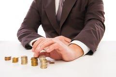 Крупный план снял рук подсчитывая монетки над белизной Стоковая Фотография