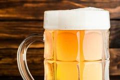 Крупный план стекла холодного пенистого пива лагера на старом деревянном backgro Стоковые Фото