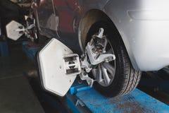 крупный план струбцины автомобиля выравнивания компьютеризировал исправленное оборудованием колесо repairshop машины Стоковое Изображение RF