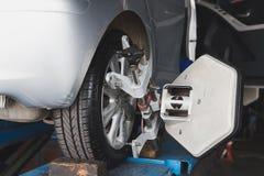 крупный план струбцины автомобиля выравнивания компьютеризировал исправленное оборудованием колесо repairshop машины Стоковые Изображения