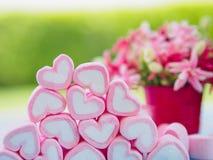 Крупный план сладостного зефира в форме сердца на деревянных плите и цветке на предпосылке Стоковые Изображения RF