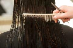 Крупный план темных влажных волос, гребня и ножниц парикмахерских услуг Стоковое Изображение
