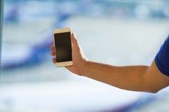 Крупный план телефона пользы молодого человека умного в авиапорте стоковое фото