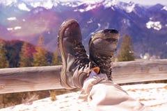 Крупный план укомплектовывает личным составом ноги и ботинки отдыхая с взглядом гор Стоковая Фотография