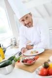 Крупный план усмехаясь кашевара подготавливая еду Стоковые Фото