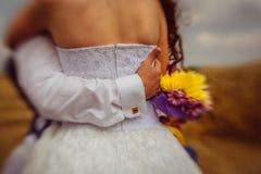 Крупный план удерживания groom задняя часть его невесты руки стоковое фото rf