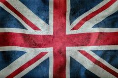 Крупный план флага Юниона Джек Флаг Великобритании Великобританский флаг Юниона Джек дуя в ветре Конкретная предпосылка Стоковые Фото